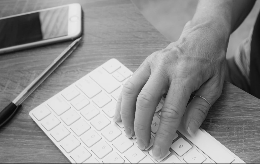 Black and white hand on computer keyboard